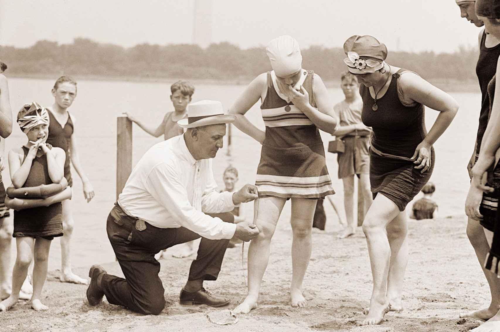 Un hombre comprueba que el largo del bañador sea el permitido.