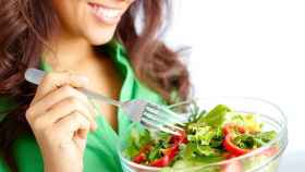Una mujer disfruta de una ensalada verde.