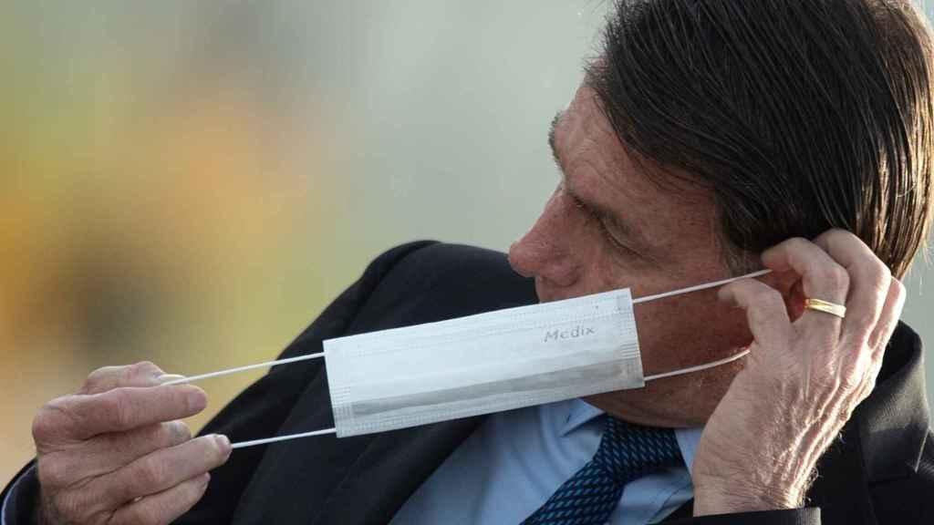 El presidente de Brasil, Jair Bolsonaro, se pone una mascarilla.