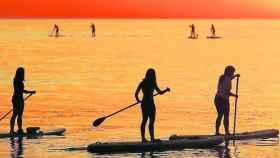 Gente practicando paddle surf en el mar