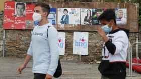 Dos jóvenes con mascarillas pasan por delante de varios carteles electorales, este viernes en Foz (Lugo).