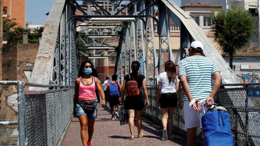 Unos vecinos cruzan el puente de la Torrassa, este sábado, en Hospitalet de Llobregat.