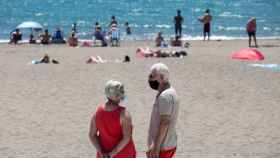 Un matrimonio usa la mascarilla en una playa de Almería.