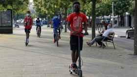 Jóvenes pasean en bicicleta y en patinete este martes en el barrio de Cap Pont, Lleida.
