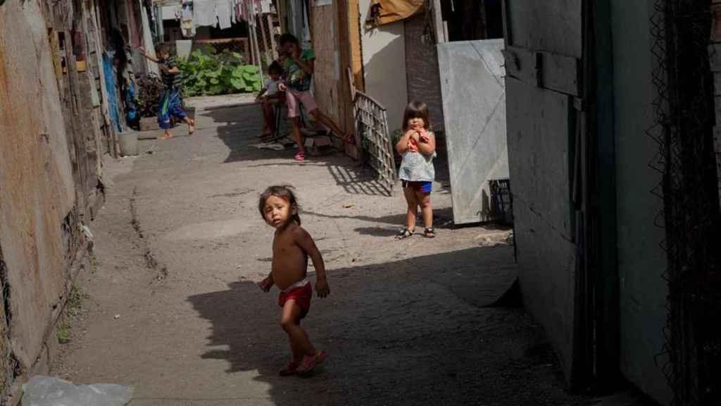 Dos niños juegan entre las viviendas improvisadas en un terreno ocupado en Caracas.