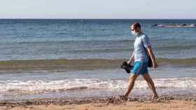 Un hombre con una mascarilla pasea por la playa