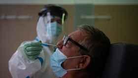 Una profesional sanitaria realiza una prueba PCR a un paciente en el CAP Raval Nord de Barcelona.