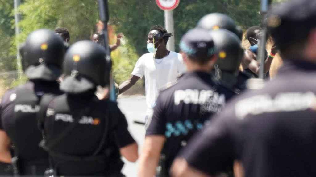 Antidisturbios y agentes de la Policía Nacional, frenando la protesta de los inmigrantes.