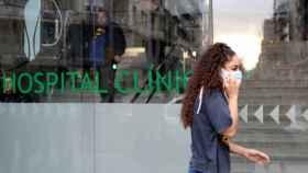 Una joven con mascarilla en la puerta del Hospital Clinic.
