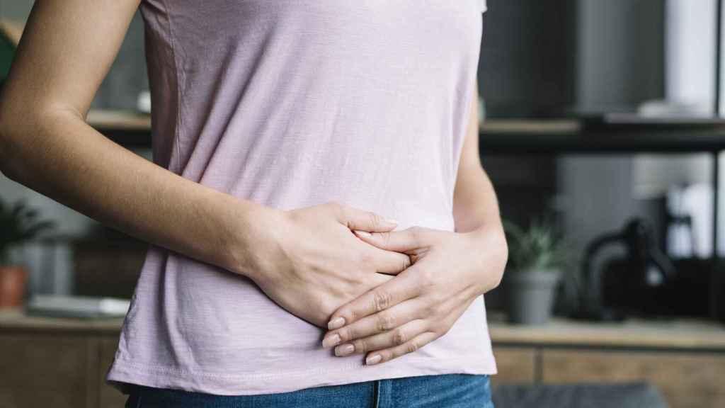 Una mujer sitúa sus manos sobre el vientre.
