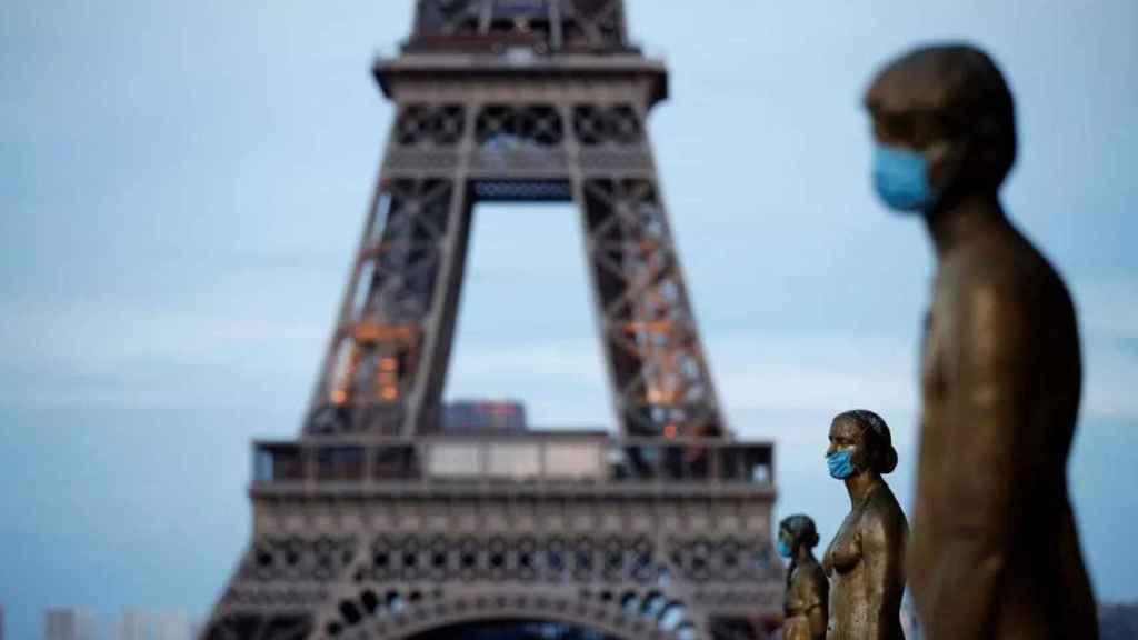 Varias estatuas con mascarilla delante de la Torre Eiffel.