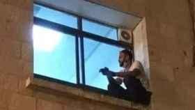 El joven palestino Jihad Al-Suwaiti contemplando a su madre a través de la ventana.