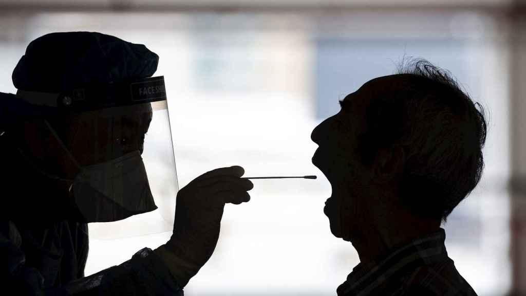 Una sanitaria se prepara a tomar muestras con hisopo del fondo de la garganta de un caso sospechoso. EFE/EPA/Jeroma Favre
