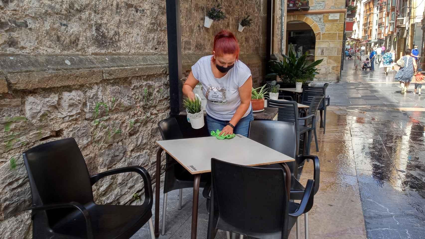Una trabajadora desinfecta la mesa de una terraza en Ermua, Vizcaya.