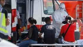 Sanitarios de la Cruz Roja atienden a varios inmigrantes que han sido interceptados tras alcanzar tierra en Alicante.