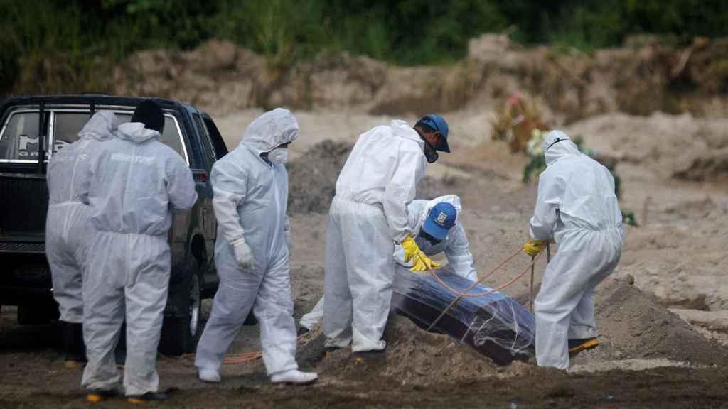 Los trabajadores del cementerio de La Bermeja, en San Salvador, entierran el ataúd de un fallecido por coronavirus.