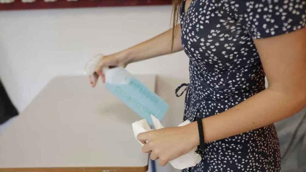 Una alumna desinfecta una mesa en el IES Alameda de Osuna de Madrid.