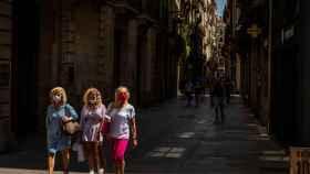 Tres mujeres con mascarilla pasean por el barrio Gótico de Barcelona.