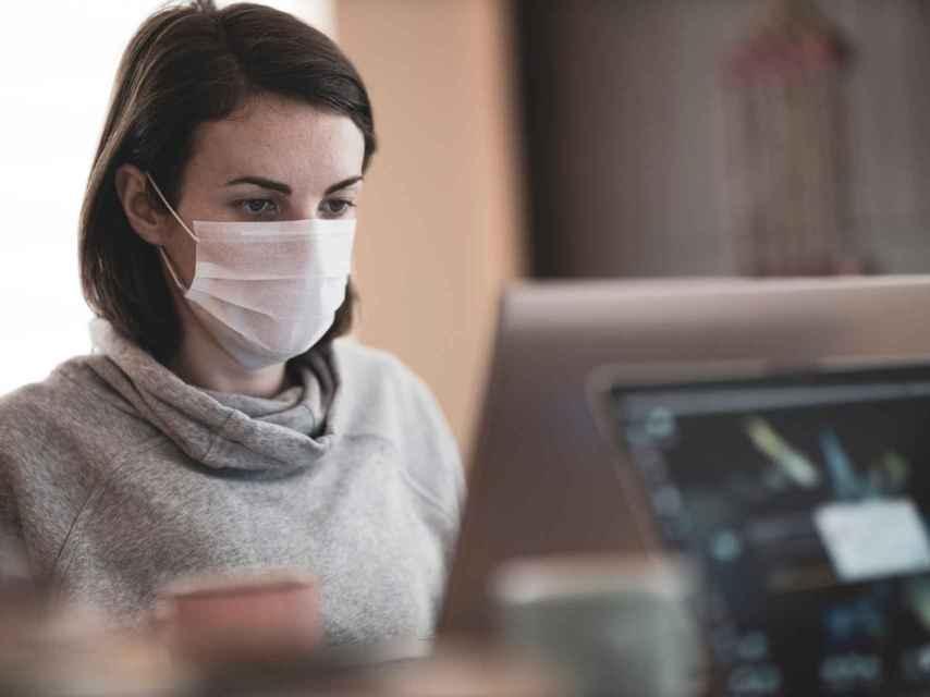 Una mujer con mascarilla en su puesto de trabajo, en una imagen de archivo.