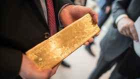 Un inversor sostiene un lingote de oro.