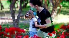 Una madre y su hija, ambas protegidas con mascarillas, en un parque de Córdoba. EFE/Salas