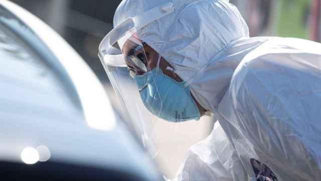 Un voluntario realizando un test PCR a una persona en un coche.