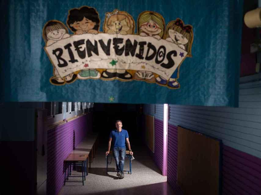El director de La Paz, tras un cartel de Bienvenidos, en el pasillo de las aulas de Infantil.