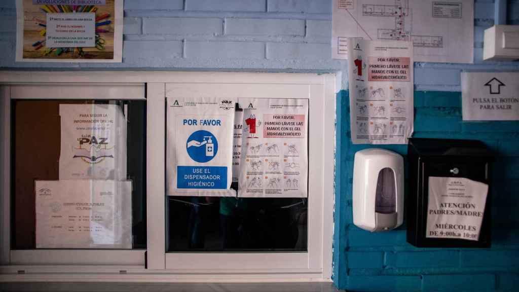 Un dispensador de gel hidroalcohólico junto a carteles informativos en la ventanilla de secretaría.