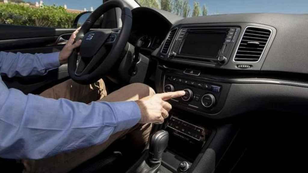 Un conductor enciende el aire acondicionado de su vehículo.