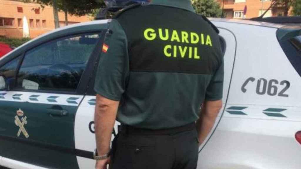 Un agente de la Guardia Civil junto a su vehículo.