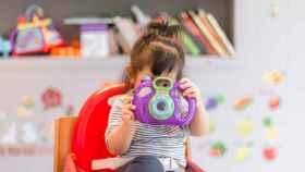 Menor con una cámara de fotos de juguete.