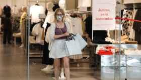 Una mujer sale de una tienda.
