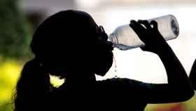Una niña bebe agua en el centro de Ourense.