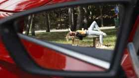 Una conductora descansa fuera de su vehículo.