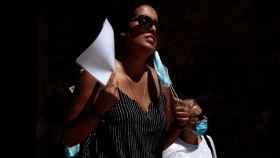 Una persona se abanica con unos documentos en una céntrica plaza de Valencia.