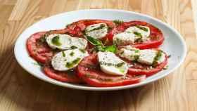 Una ensalada de tomate con un poquito de queso.
