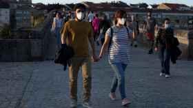 Varias personas pasean por el Puente Romano de Ourense.