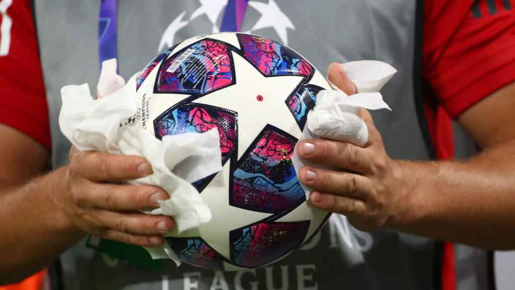 Un recogepelotas desinfecta un balón de la Champions League