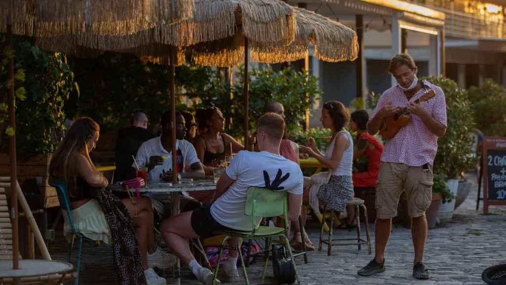 Consumidores en terrazas junto a un artista callejero en Barcelona.