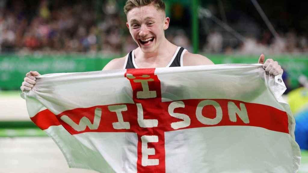 Nile Wilson, con la bandera de Inglaterra tras ganar la medalla en barra fija