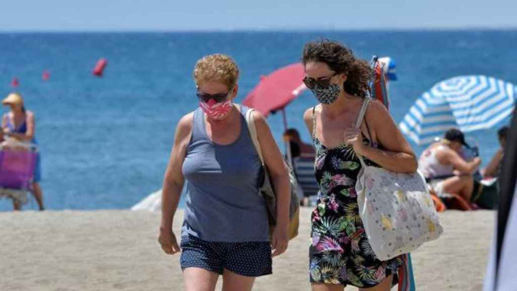 Un hombre y una mujer paseando en la playa con mascarilla.