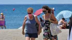Dos mujeres con mascarilla en la playa.