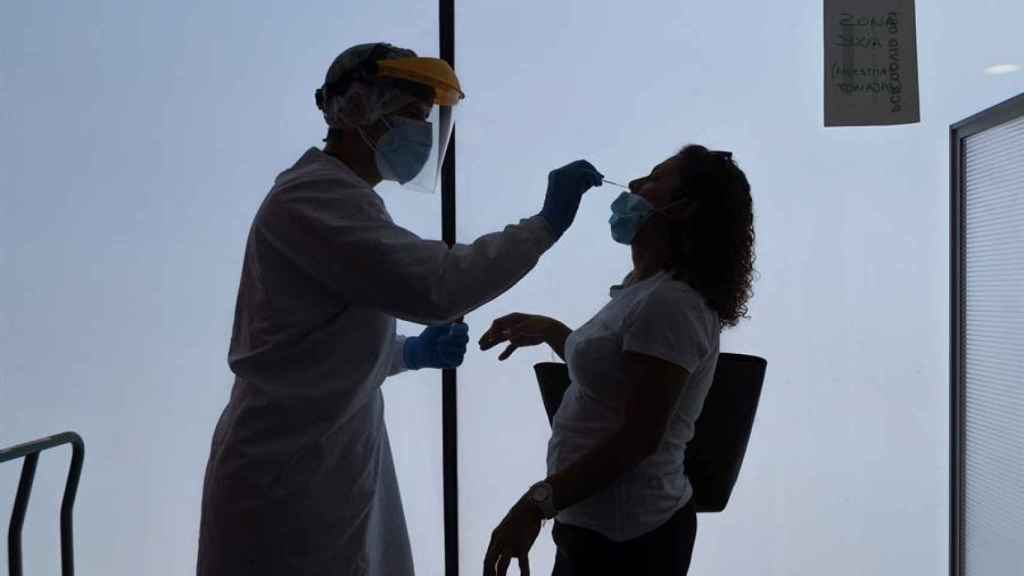 Un sanitario realiza una prueba PCR a una joven.