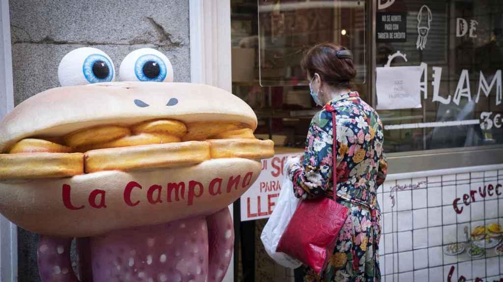 Una mujer espera a ser atendida en Bar La Campana, en Madrid.