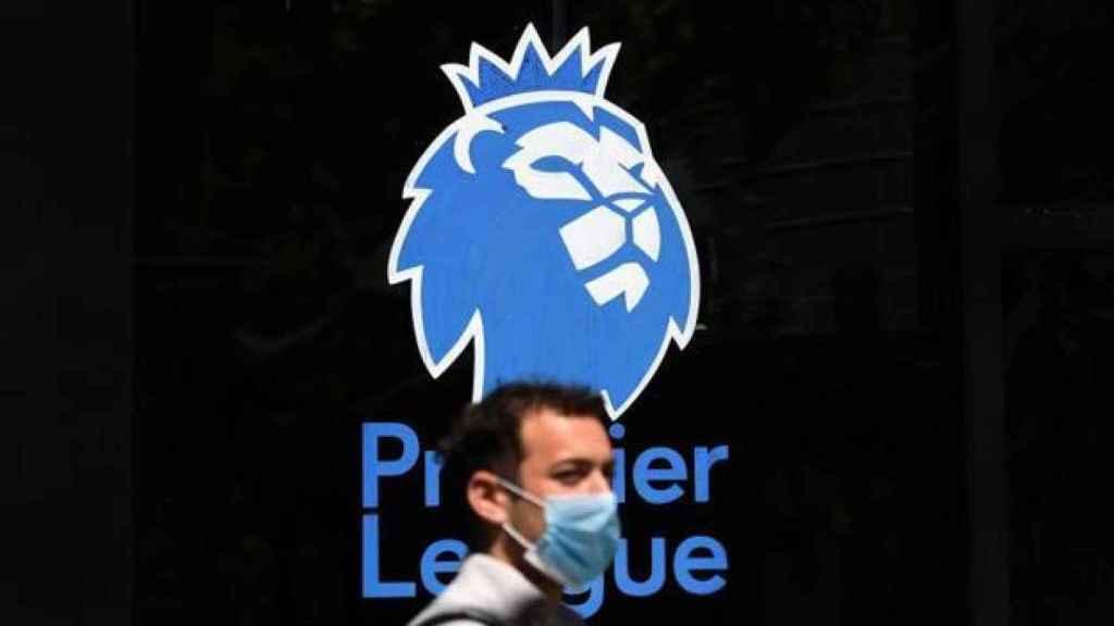Un hombre con mascarilla frente al logo de la Premier League