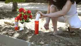 Una mujer enciende una vela junto a un ramo de flores en el lugar donde una mujer ha muerto en Segovia.