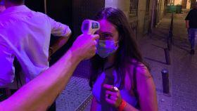 Toman la temperatura a una chica, a la entrada de una discoteca.
