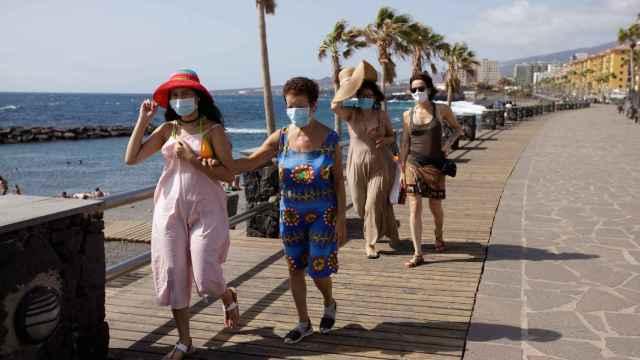 Unos turistas caminan por un paseo cercano a la playa de Las Caletillas, en Tenerife.