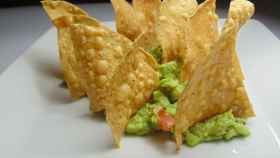 Uno nachos triangulares sobre un poco de guacamole.