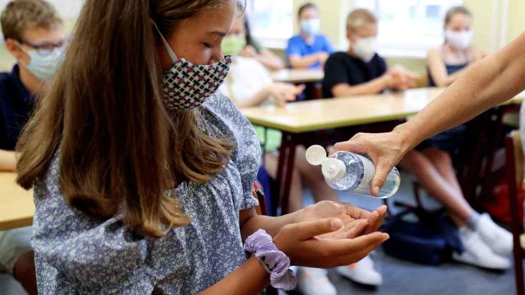 Una estudiante europea recibe solución hidroalcohólica en la escuela.